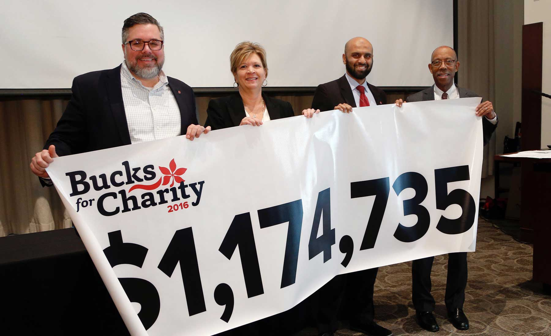 Mike Hofherr, Marti Taylor, Mamoon Syed and President Drake with the total displayed on a banner