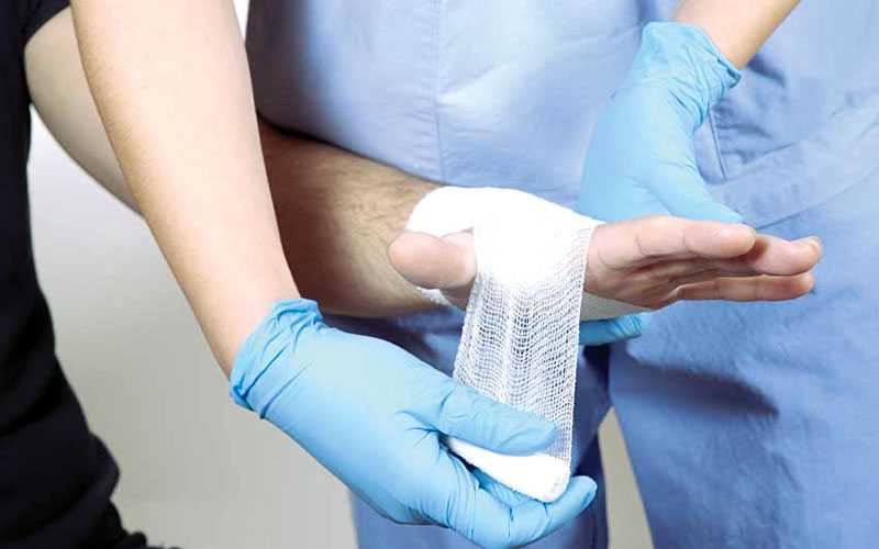 closeup of nurse wrapping a bandage around hand