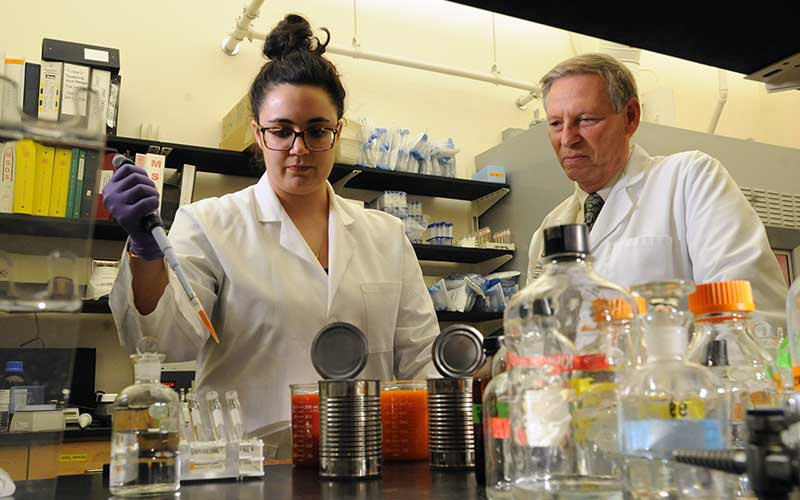 Female researcher using dropper to extract liquid while professor observes